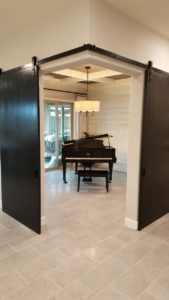 grand piano music room with converging barn doors featuring Goldberg Brothers barn door hardware and  corner converging guide bracket