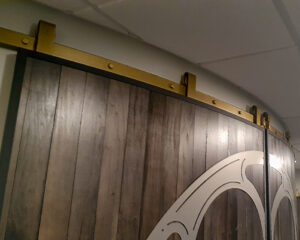 gold-colored barn door hardware on a pair of large, curved doors against a curved wall in an office
