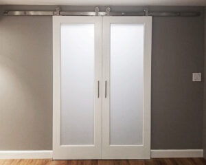 White, biparting closet doors with Goldberg Brothers stainless steel top-mount barn door hardware