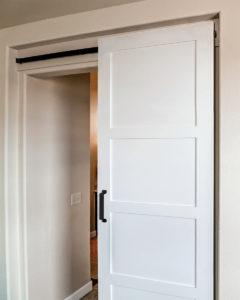 white sliding bathroom door with hidden style barn door hardware