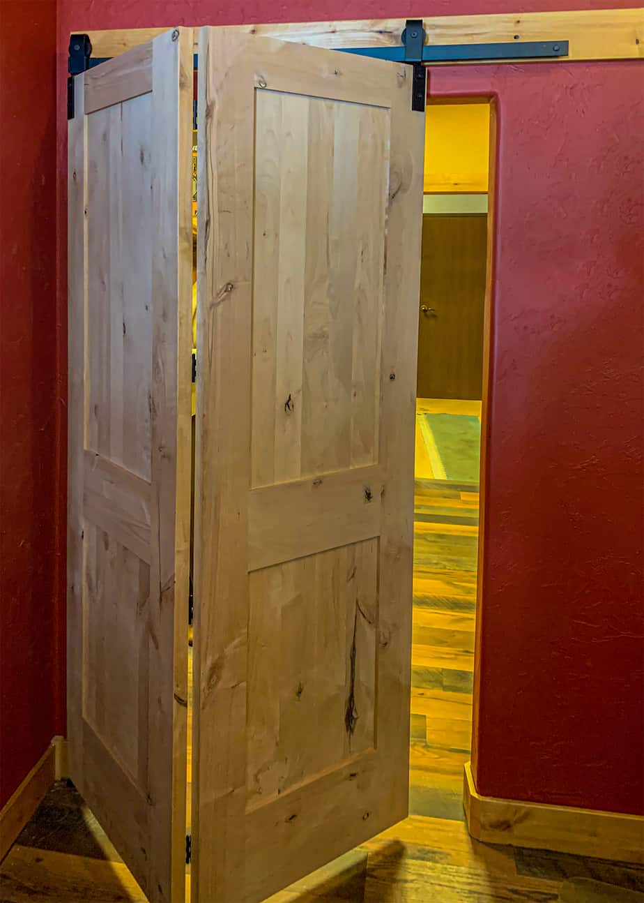 Barnfold folding barn door hardware on a pine door against a red wall