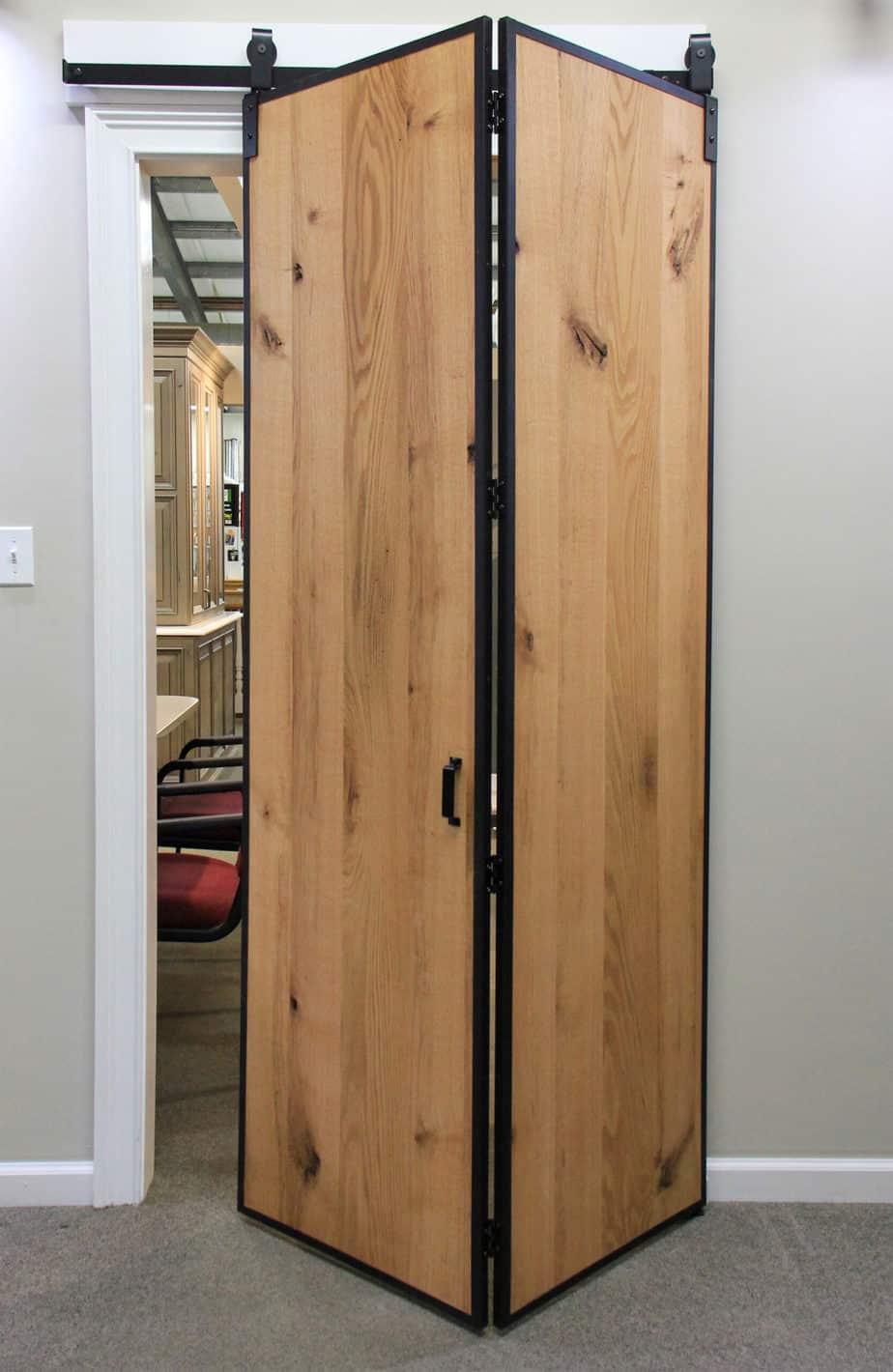 Partially closed Barnfold folding barn door hardware and Barn Door Edge Wrap in a showroom display
