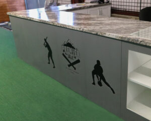 A customer service counter covered with Goldberg Brothers MClad steel panels and laser-etched with business logos