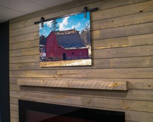 Mini-sized barn door hardware adorns a decorative print of an old barn, mounted above a shiplap fireplace.