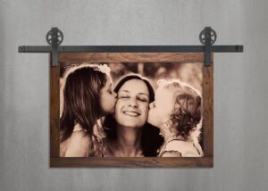 A photo print of a mother and two young daughters is mounted in a wood frame suspended by steel barn door-style roller hangers and track.