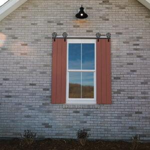wagon wheel dummy barn door hardware on brick home with decorative red shutters