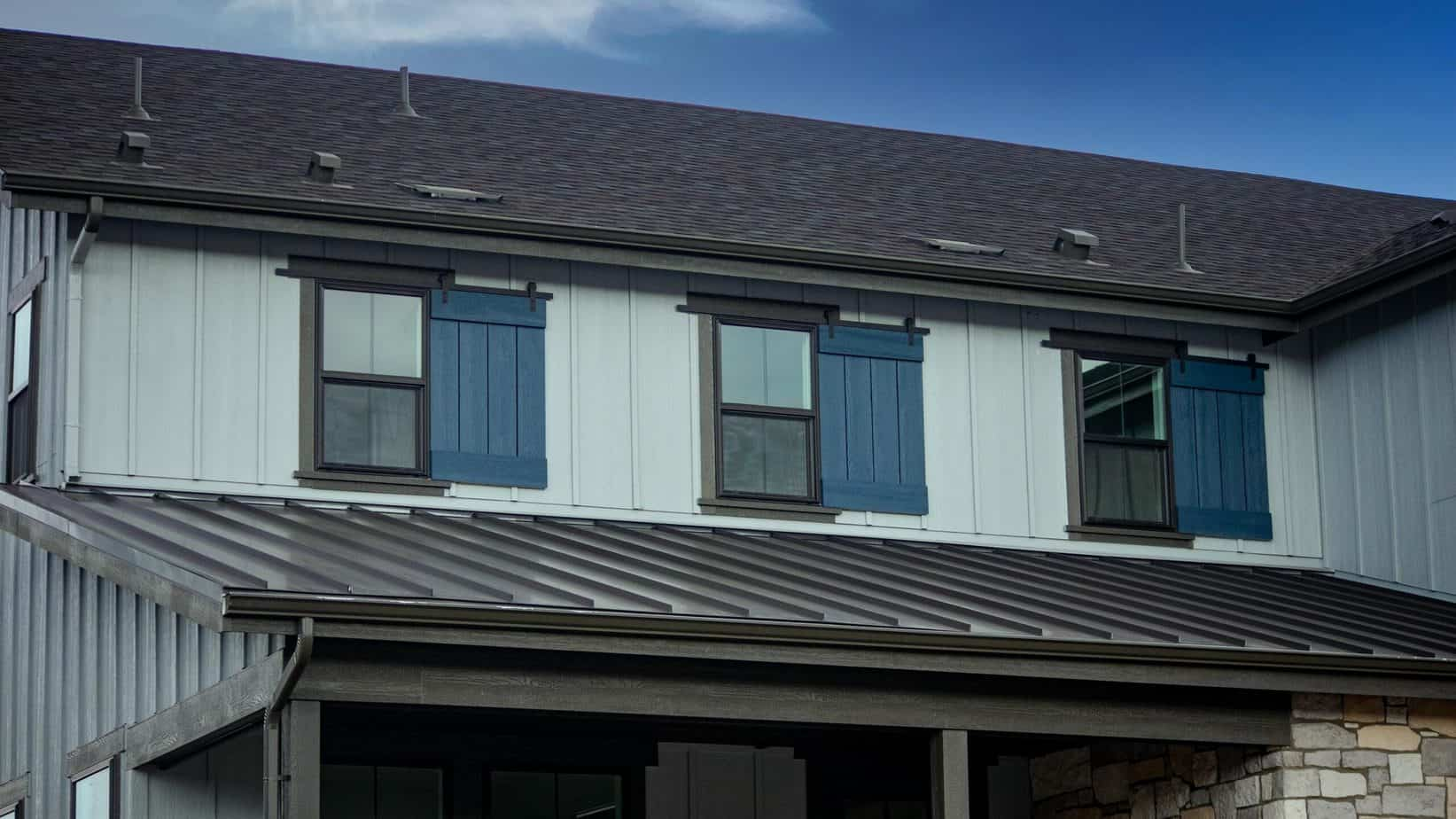 Gray house with three windows featuring decorative blue shutters and Goldberg Brothers dummy barn door hardware