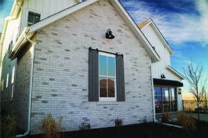 A gray brick home has a window adorned with a pair of decorative gray shutters that have barn door-style steel hardware attached to the top.